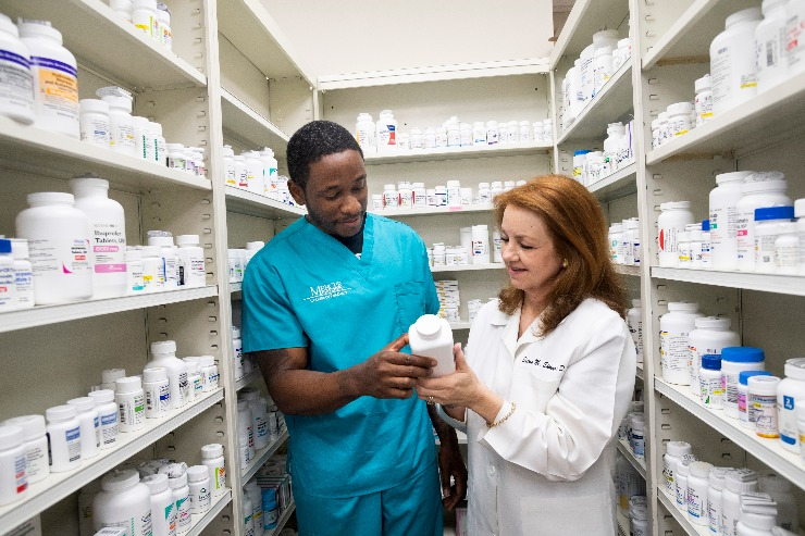 A pharmacy student works with a pharmacist